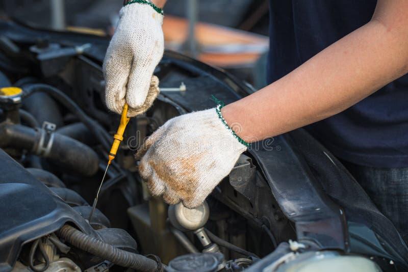Χέρια του πετρελαίου μηχανών αυτοκινήτων ελέγχου τεχνικών, εκλεκτική εστίαση στοκ εικόνα με δικαίωμα ελεύθερης χρήσης