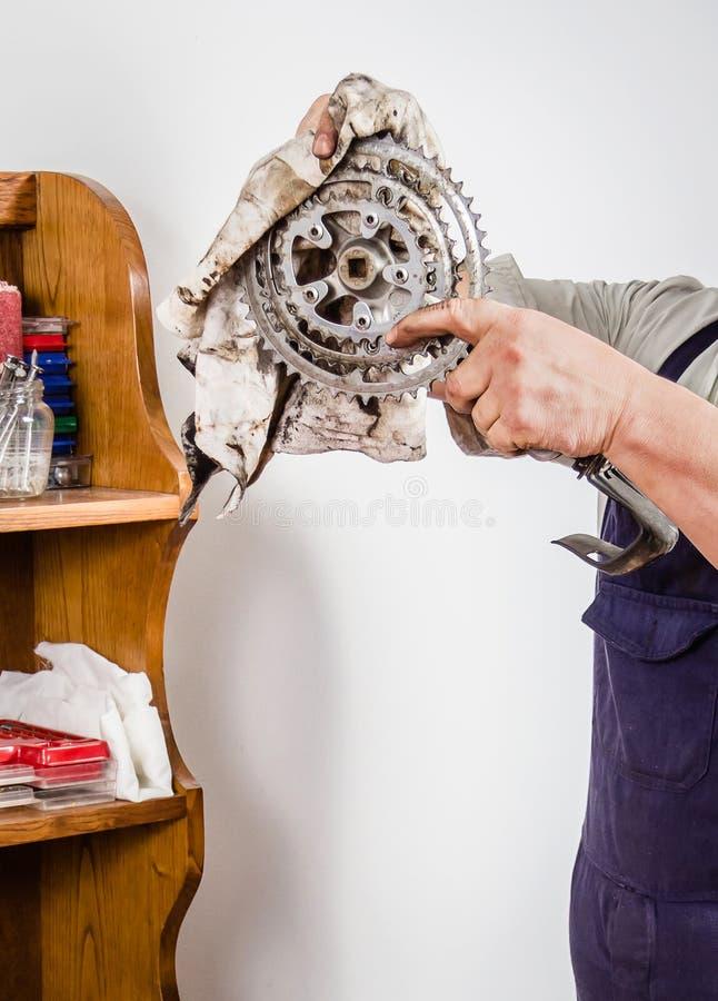 Χέρια του πραγματικού μηχανικού ποδηλάτων που καθαρίζει το ασταθές σύνολο στοκ εικόνα