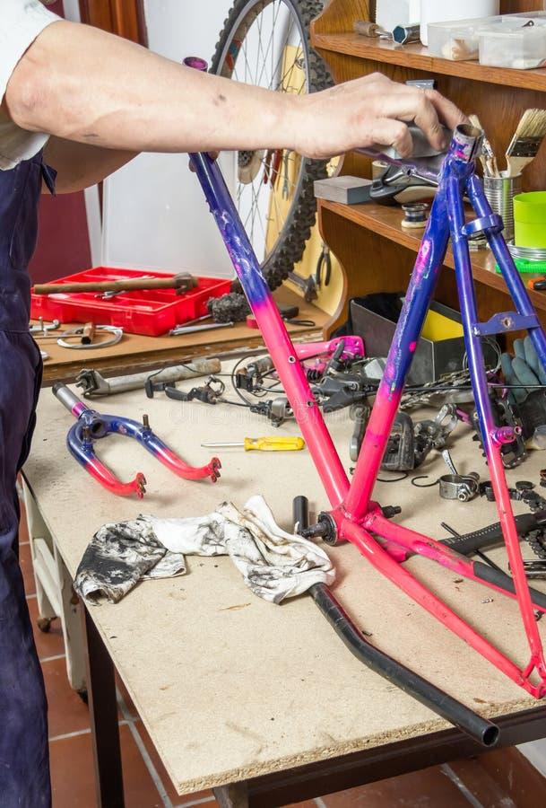 Χέρια του πραγματικού ποδηλάτου πλαισίων ποδηλάτων μηχανικού στρώνοντας με άμμο στοκ φωτογραφίες