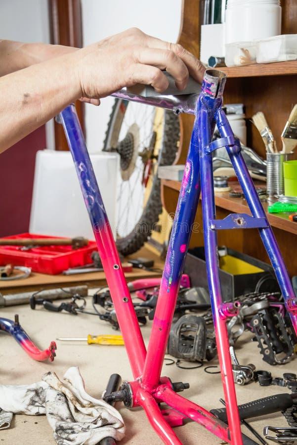 Χέρια του πραγματικού ποδηλάτου πλαισίων ποδηλάτων μηχανικού στρώνοντας με άμμο στοκ εικόνες