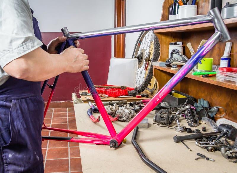 Χέρια του πραγματικού ποδηλάτου πλαισίων ποδηλάτων μηχανικού καθαρίζοντας στοκ εικόνες