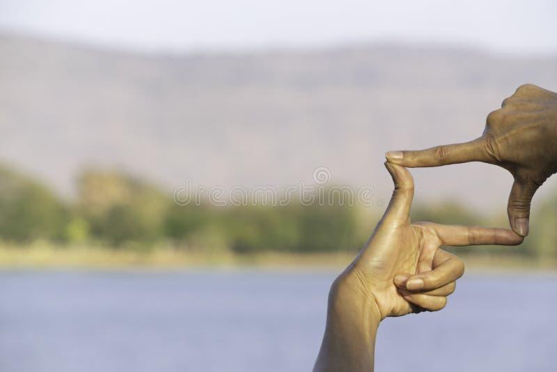 Χέρια του προσώπου που κάνει την απόσταση ή το σύμβολο πλαισίων στη φύση στοκ εικόνες