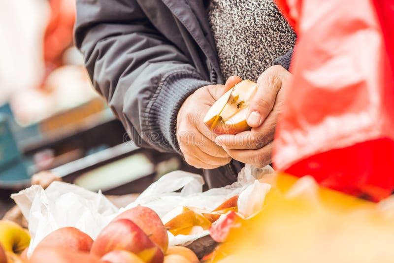 Χέρια του τέμνοντος μήλου ατόμων με το μαχαίρι στοκ εικόνες