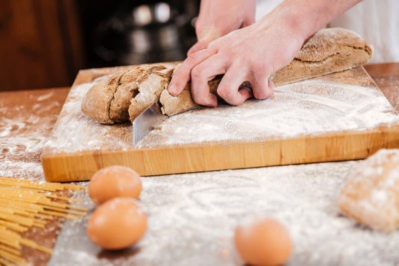Χέρια του τέμνοντος ψωμιού αρτοποιών ατόμων στον ξύλινο πίνακα στοκ φωτογραφία