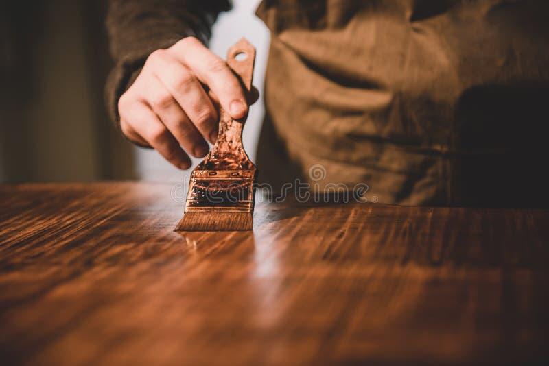 Χέρια του χειροτεχνικού πιό luthier λουστραρίσματος, που χτίζουν μια διπλή πέρκα στοκ εικόνα
