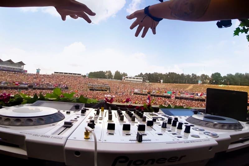 Χέρια του DJ επάνω από το όργανο ελέγχου του κανονισμού των υγιών συχνοτήτων DJ στη συναυλία για τον τηλεχειρισμό στοκ εικόνα