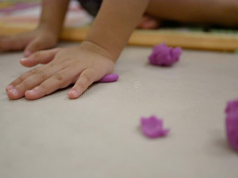 Χέρια το λίγο μωρών ` s που παίζουν τη ζύμη παιχνιδιού στο πάτωμα στοκ φωτογραφία