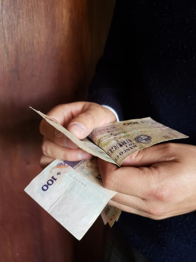 χέρια τραπεζογραμματίων των μετρώντας Ουρουγουανών ατόμων στοκ φωτογραφίες