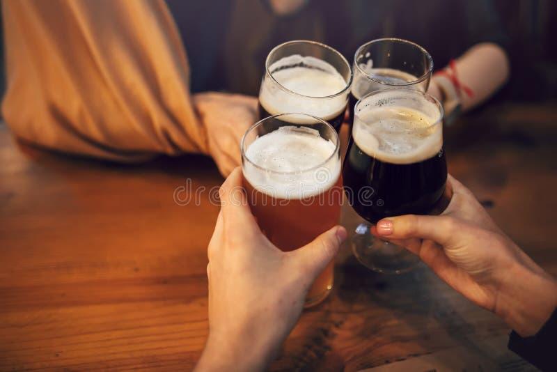 Χέρια των ανθρώπων που κρατούν την μπύρα και ενθαρρυντικός στο μπαρ ζυθοποιείων άνθρωποι στοκ φωτογραφία