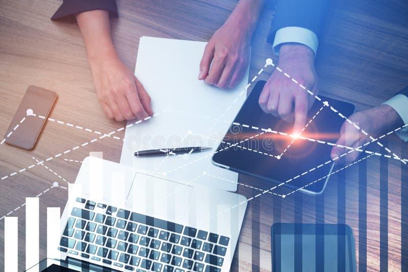Χέρια των επιχειρηματιών με τις συσκευές, γραφικές παραστάσεις στοκ φωτογραφία με δικαίωμα ελεύθερης χρήσης