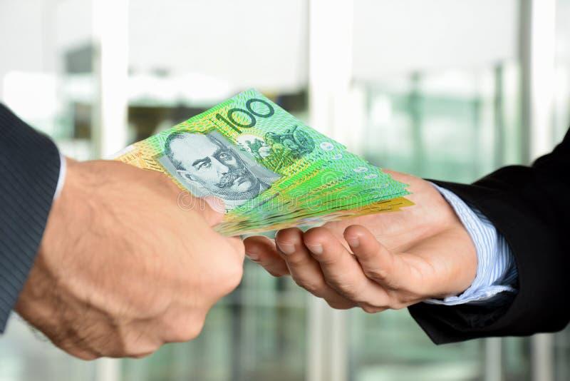 Χέρια των επιχειρηματιών που περνούν τα χρήματα, τραπεζογραμμάτια δολαρίων της Αυστραλίας στοκ εικόνες