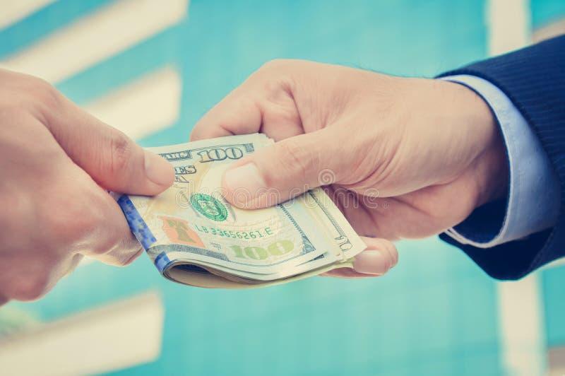 Χέρια των επιχειρηματιών που περνούν τα χρήματα στοκ φωτογραφία