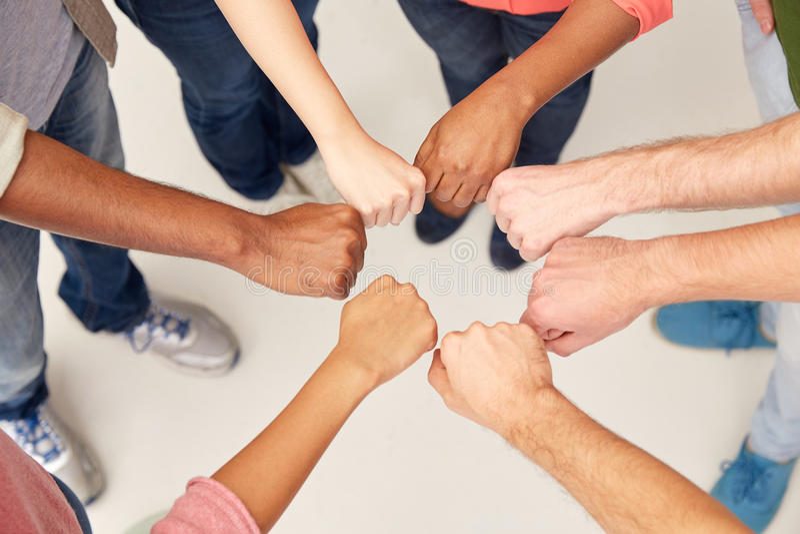 Χέρια των διεθνών ανθρώπων που κάνουν την πρόσκρουση πυγμών στοκ εικόνα