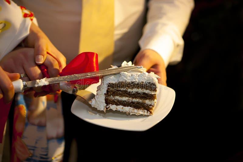 Χέρια των newlyweds με τα δαχτυλίδια και το κόκκινο τόξο, και γαμήλιο κέικ σε ένα πιάτο στοκ φωτογραφία