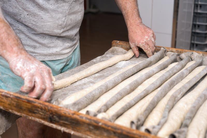 Χέρια Baker που προετοιμάζουν τις άψητες φραντζόλες ψωμιού έτοιμες να ψήσουν στοκ εικόνα με δικαίωμα ελεύθερης χρήσης