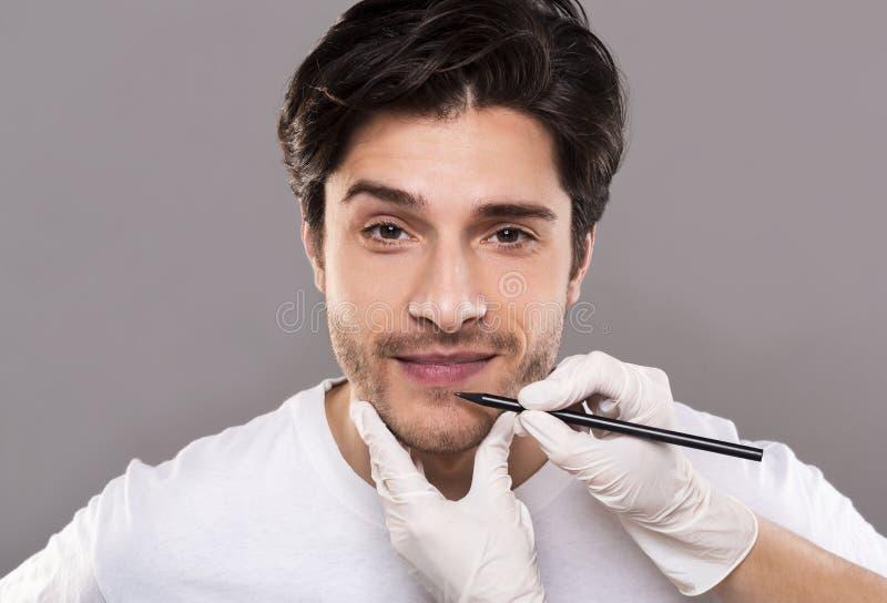 Χέρια Beautician που χαρακτηρίζουν το αρσενικό πρόσωπο πριν από τη λειτουργία ομορφιάς στοκ φωτογραφία με δικαίωμα ελεύθερης χρήσης