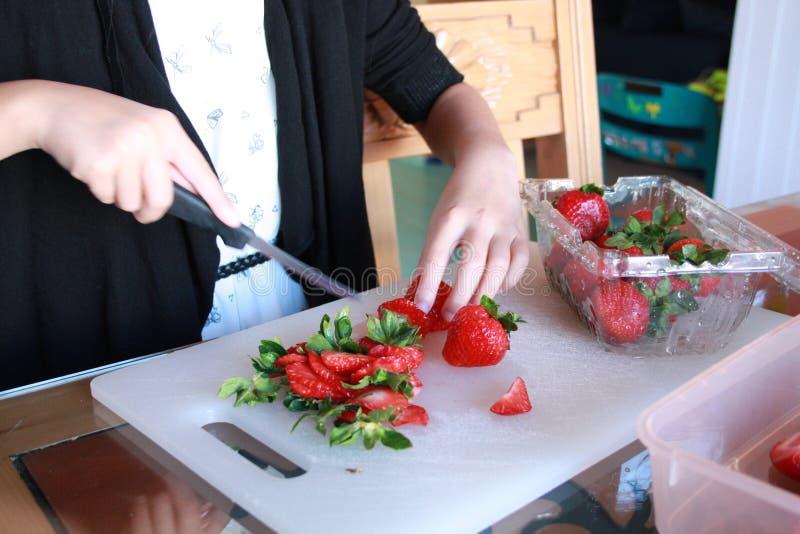 Χέρια Childs που κόβουν τις φράουλες στοκ εικόνα
