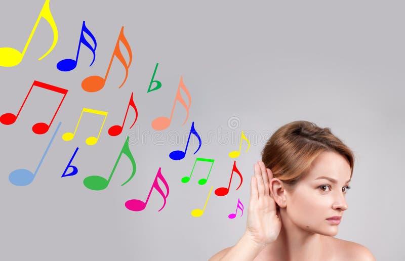 Χέρι λαβής γυναικών κοντά στη μουσική της αυτιών και ακούσματος στοκ φωτογραφία με δικαίωμα ελεύθερης χρήσης