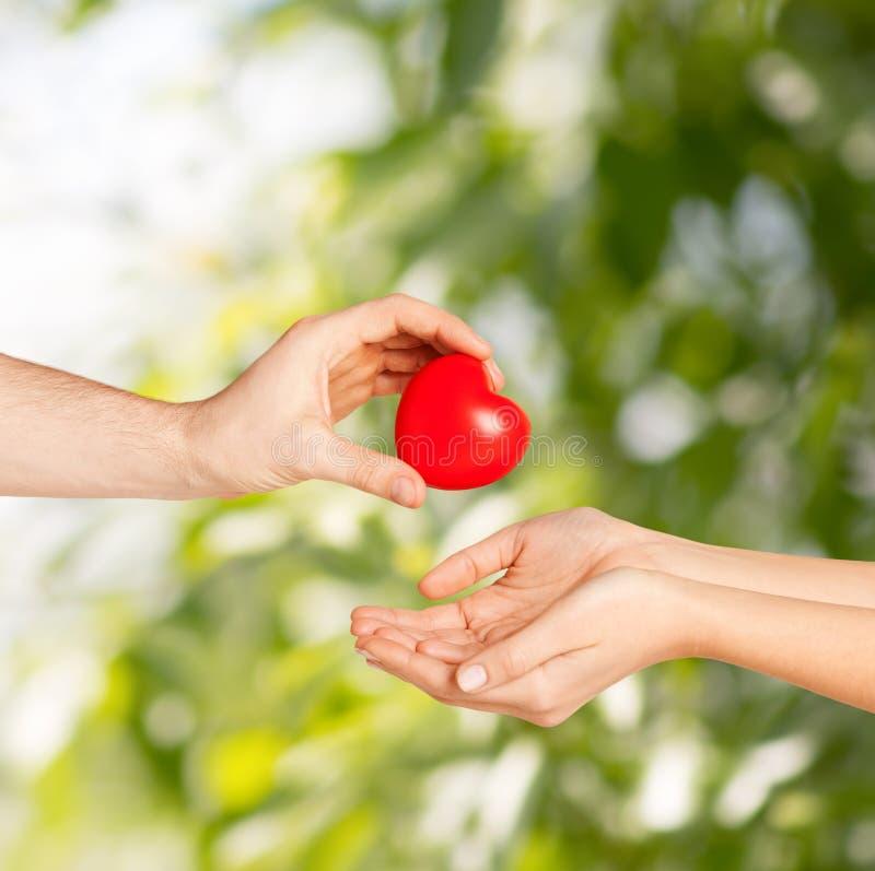 Χέρι ανδρών που δίνει την κόκκινη καρδιά στη γυναίκα στοκ εικόνες με δικαίωμα ελεύθερης χρήσης