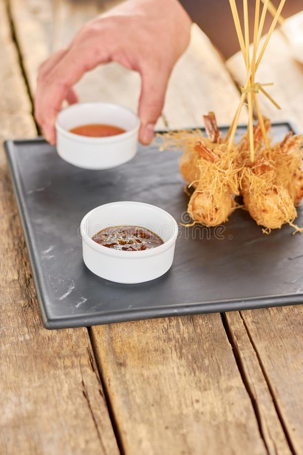 Χέρι αρχιμαγείρων που βάζει τη σάλτσα στις τριζάτες γαρίδες στοκ φωτογραφίες