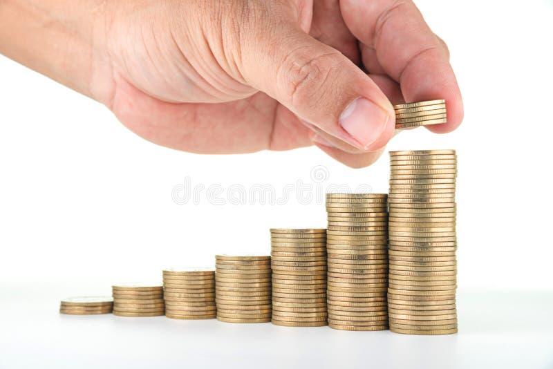 Χέρι ατόμων που βάζει τα χρήματα στους σωρούς νομισμάτων αύξησης στο άσπρο υπόβαθρο στοκ εικόνα