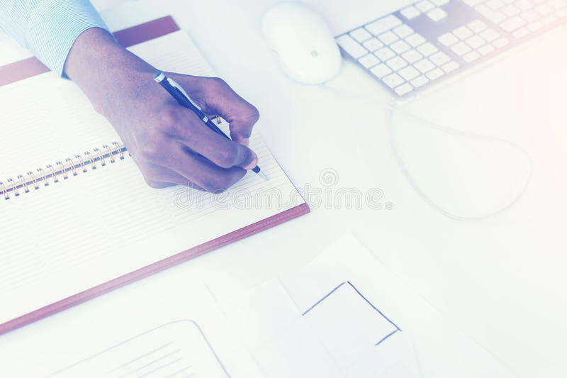 Χέρι ατόμων που γράφει στο σημειωματάριο στοκ εικόνα με δικαίωμα ελεύθερης χρήσης