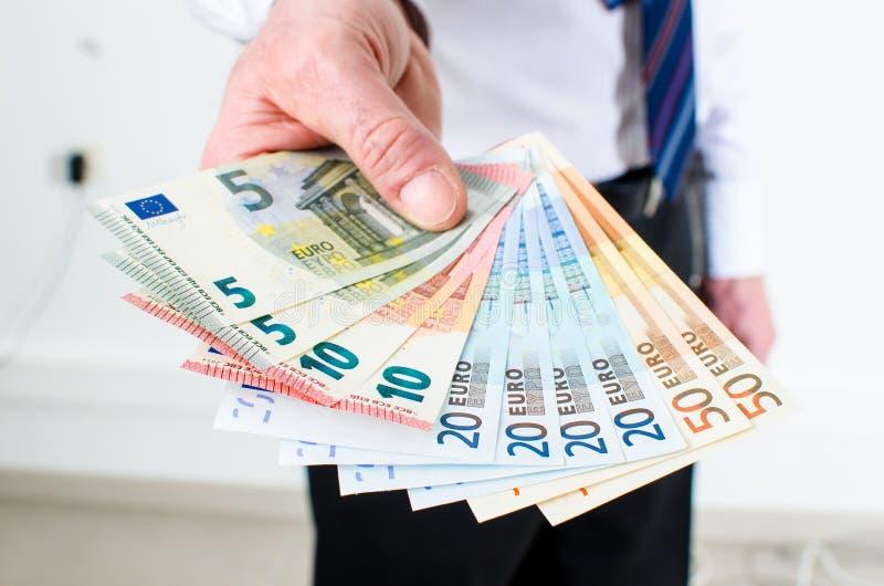 Χέρι ατόμων που κρατά τις ευρο- σημειώσεις στοκ εικόνες