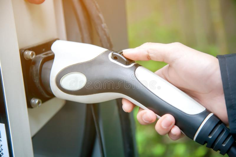 Χέρι ατόμων που κρατά το ηλεκτρικό βούλωμα για τη χρέωση του ηλεκτρικού αυτοκινήτου στοκ εικόνες με δικαίωμα ελεύθερης χρήσης