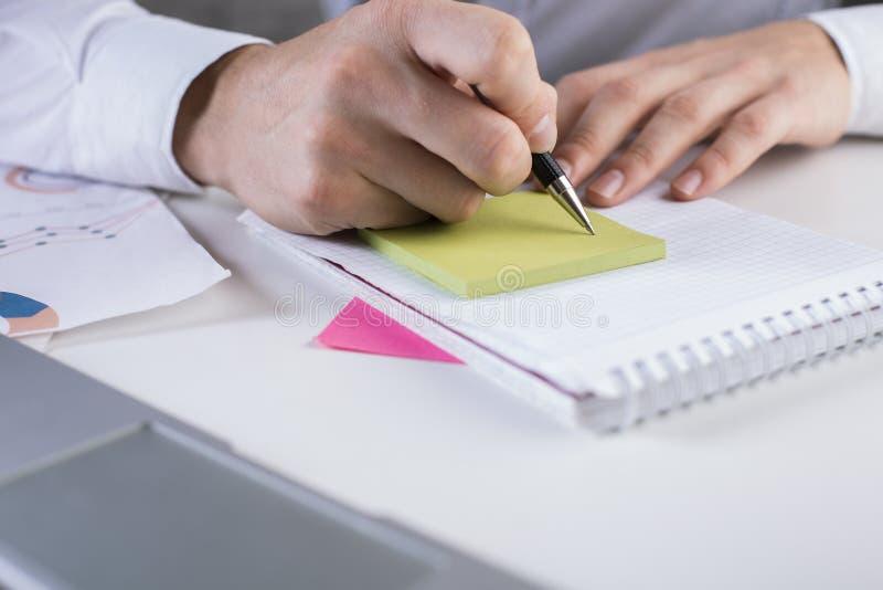 Χέρι ατόμων ` s που γράφει στο σημειωματάριο στοκ φωτογραφία
