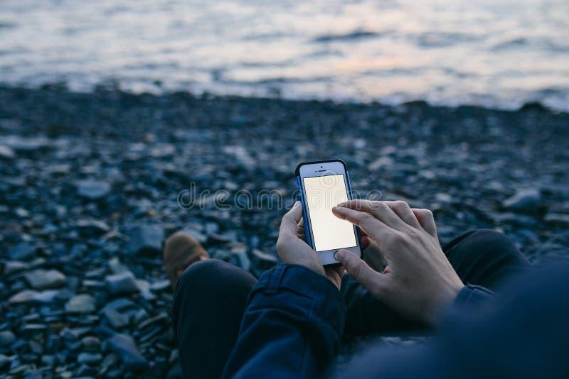 Χέρι ατόμων ` s που κρατά ένα τηλέφωνο στο υπόβαθρο της παραλίας στοκ εικόνα