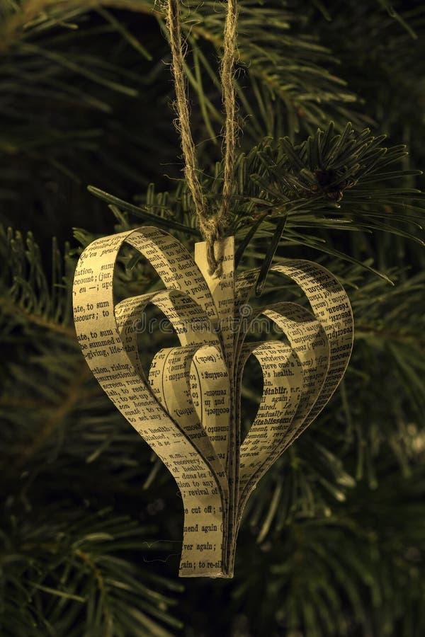 Χέρι - γίνοντα παιχνίδι Χριστουγέννων μορφής καρδιών εγγράφου στο δέντρο στοκ εικόνες με δικαίωμα ελεύθερης χρήσης