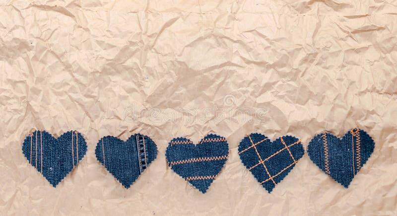 Χέρι - γίνοντες καρδιές τζιν σε ένα τσαλακωμένο υπόβαθρο εγγράφου τεχνών Επίπεδος βάλτε, τοπ άποψη, ελάχιστο ύφος, διάστημα αντιγ στοκ εικόνα με δικαίωμα ελεύθερης χρήσης