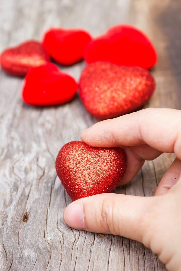 Χέρι γυναίκας που κρατά μια κόκκινη μορφή καρδιών στοκ φωτογραφίες με δικαίωμα ελεύθερης χρήσης