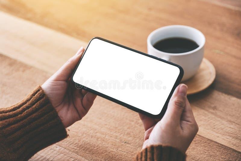 Χέρι γυναίκας που κρατά το μαύρο κινητό τηλέφωνο με την κενή οθόνη οριζόντια με το φλυτζάνι καφέ στον ξύλινο πίνακα στοκ φωτογραφίες