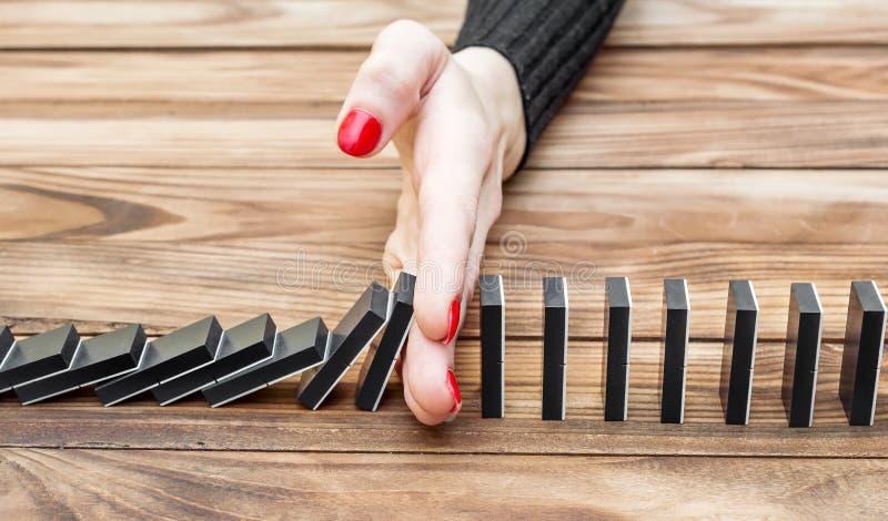 Χέρι γυναίκας που σταματά την επίδραση ντόμινο στο γραφείο στοκ φωτογραφία