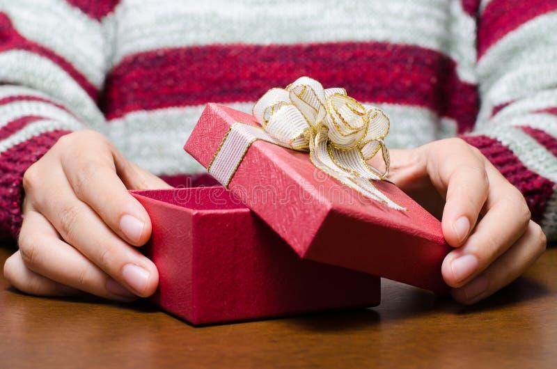 Χέρι γυναικών που ανοίγει το κόκκινο κιβώτιο δώρων για το δόσιμο στοκ εικόνες