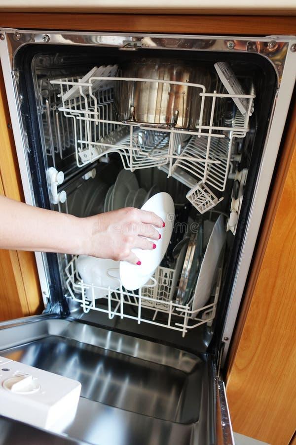 Χέρι γυναικών που βάζει τα βρώμικα πιάτα στο πλυντήριο πιάτων στοκ εικόνες με δικαίωμα ελεύθερης χρήσης