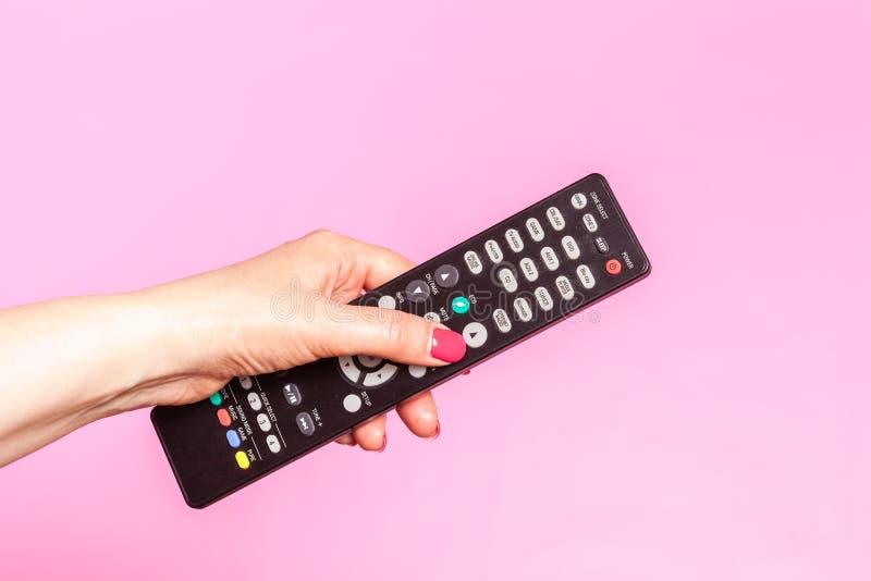 Χέρι γυναικών που κρατά τον τηλεχειρισμό, σχετικά με το ρόδινο υπόβαθρο στοκ εικόνα