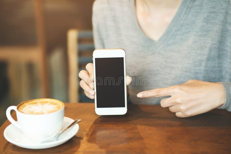 Χέρι γυναικών που κρατά το κινητό έξυπνο τηλέφωνο με την κενή οθόνη υπολογιστών γραφείου στοκ εικόνες με δικαίωμα ελεύθερης χρήσης