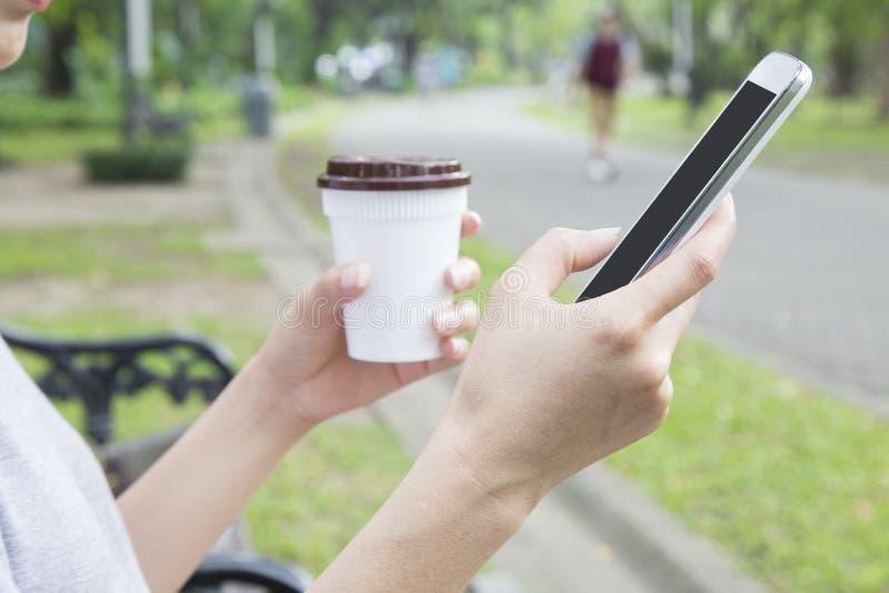 Χέρι γυναικών που κρατά το κινητό τηλέφωνο και το μαύρο καφέ πλαστικό φλυτζάνι και στοκ εικόνες