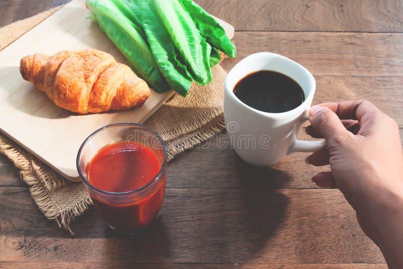 Χέρι γυναικών που κρατά το μαύρο φλυτζάνι καφέ με το υγιές πρόγευμα στον ξύλινο πίνακα στοκ φωτογραφία
