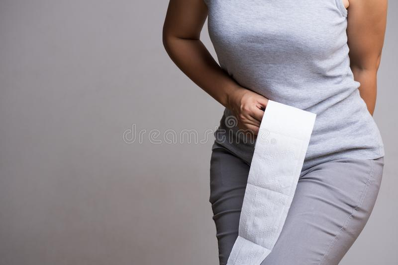 Χέρι γυναικών που κρατά το ρόλο της κατώτατων σημείων και ιστού ή χαρτιού τουαλέτας Αναταραχή, διάρροια, δυσκοιλιότητα όντας χέρι στοκ φωτογραφία