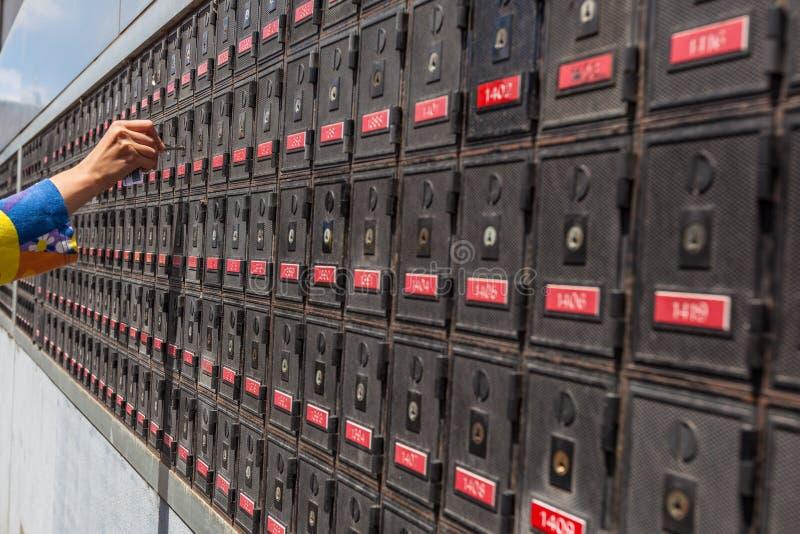 Χέρι γυναικών που ξεκλειδώνει την ταχυδρομική θυρίδα στοκ φωτογραφία