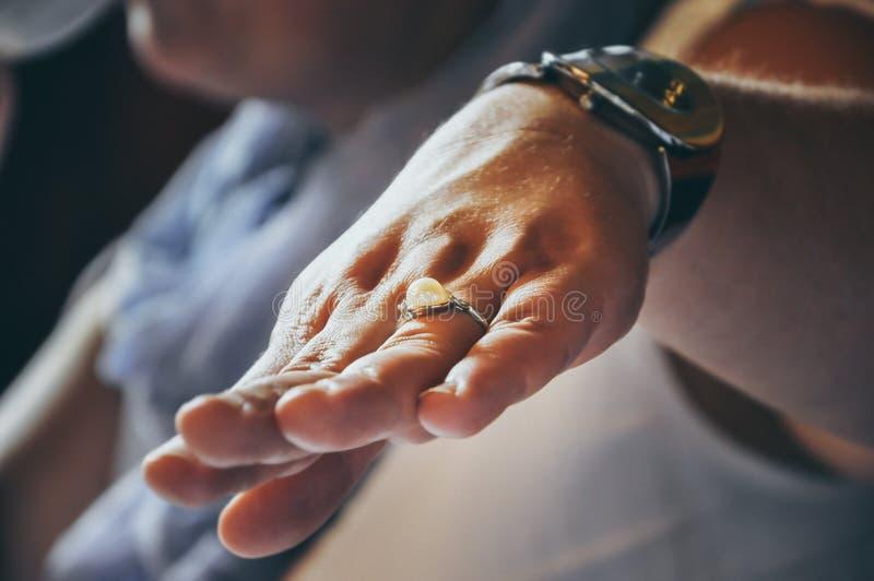 Χέρι γυναικών που παρουσιάζει το ασημένιο δαχτυλίδι με το μαργαριτάρι στοκ φωτογραφίες