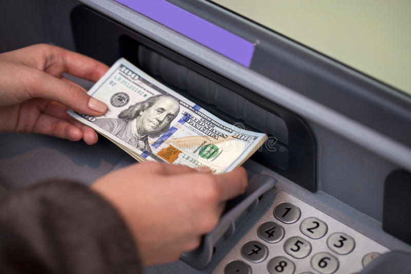 Χέρι γυναικών που παρουσιάζει τραπεζογραμμάτια δολαρίων μπροστά από το ATM στοκ εικόνα