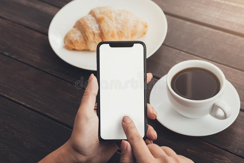 Χέρι γυναικών που χρησιμοποιεί το κενό έξυπνο τηλέφωνο κατά τη διάρκεια του προγεύματος στοκ φωτογραφία με δικαίωμα ελεύθερης χρήσης