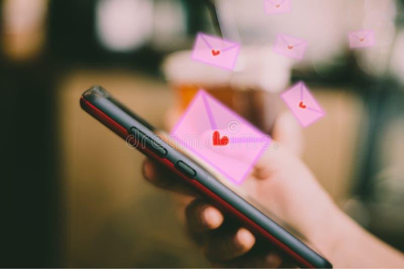 Χέρι γυναικών που χρησιμοποιεί το smartphone για να στείλει την επιστολή αγάπης ηλεκτρονικού ταχυδρομείου στοκ εικόνες
