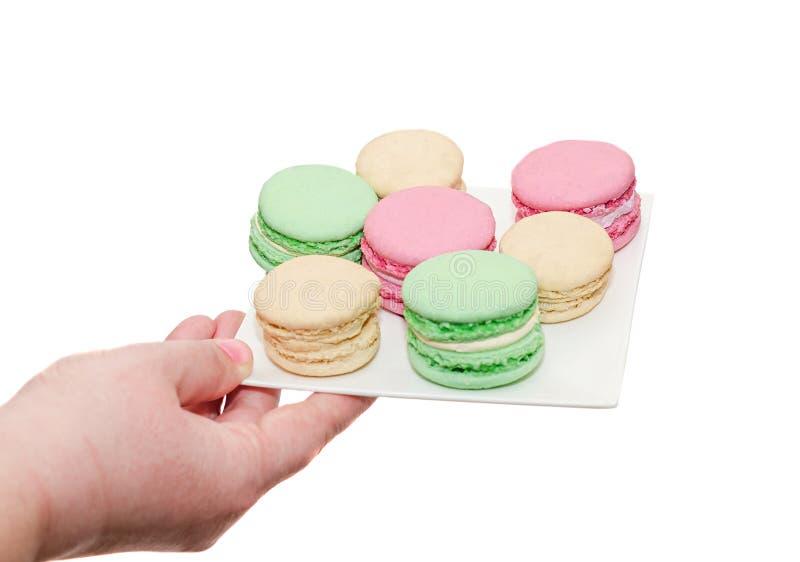 Χέρι γυναικών holdin ένα άσπρο πιάτο με χρωματισμένα γλυκά macaroons, FR στοκ εικόνες