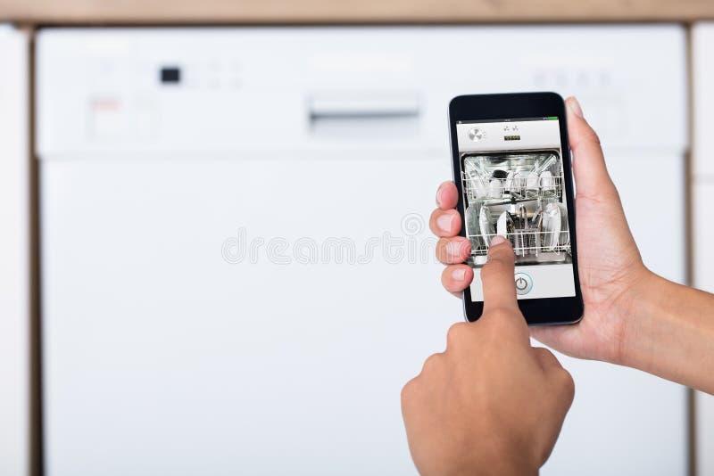 Χέρι γυναικών ` s που παρουσιάζει πλυντήριο πιάτων App στοκ εικόνες