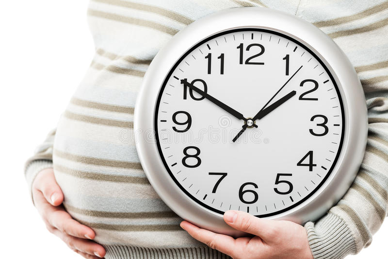 Χέρι εγκύων γυναικών που κρατά το μεγάλο ρολόι τοίχων γραφείων που παρουσιάζει χρόνο στοκ εικόνες με δικαίωμα ελεύθερης χρήσης